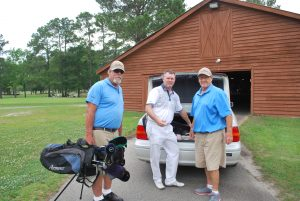Matt Palmer, Shawn Denney and David Marr load golf clubs for delivery to Fort Bragg